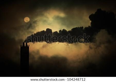 Sun shines through smoke from factory chimneys, telephoto shot. - stock photo
