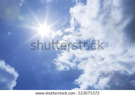 Sun shining at cloudy blue sky with copy space