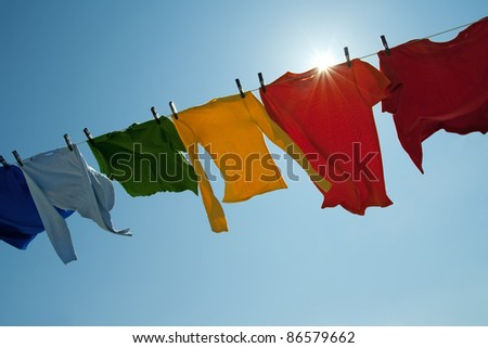 Sun shining over a laundry line with bright clothes on a windy day. - stock photo