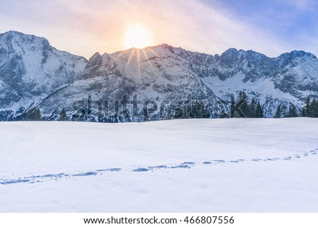 Sun shining over mountain peaks and snow Lovely winter scenery with the Austrian Alps mountains covered in snow, the trees line and a route from footsteps in the snow.