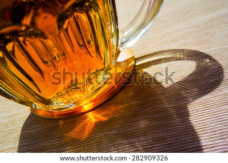 Sun shining through Czech draught beer in glass at restaurant - stock photo