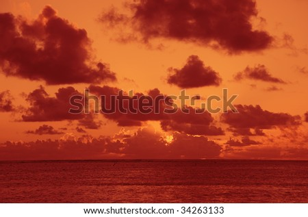 Sun shining through dark Clouds at Sunset over South Pacific Ocean - stock photo