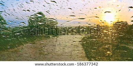 Sun shower. Drops of rain on windscreen against sunset - stock photo