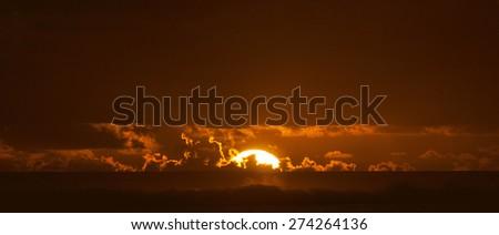 Sun sinks to Sea - Behind Coral Reef of Rarotonga, Cook Islands, Polynesia - stock photo