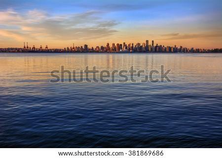 Sun spotlights the city from afar and serene ocean - stock photo