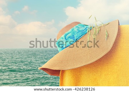 Sun straw hat and towel. Sunny beach colorful accessories with sea landscape in the background. Toned colors vintage photo - stock photo