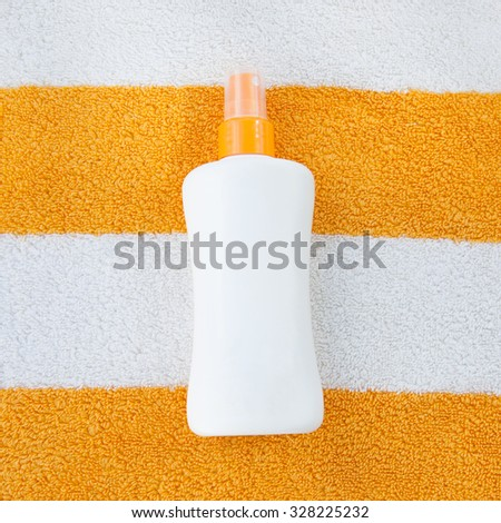 Sun tan spray lotion in white bottle lying on the white and orange striped beach towel background. - stock photo