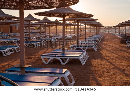 Sun umbrella and beach beds on tropical coastline - stock photo
