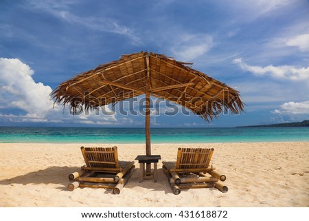Sun umbrella and deckchairs on white sand tropical beach. Summer vacation concept. - stock photo