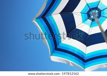 Sun umbrella over blue sky - stock photo