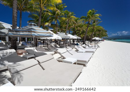 Sun umbrellas and beach beds on tropical coastline, Philippines, Boracay  - stock photo