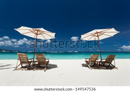Sun umbrellas and beach chairs on tropical beach, Philippines, Boracay