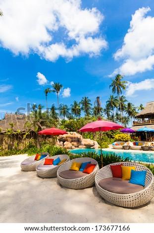 Sun umbrellas and beach chairs on tropical coast - stock photo