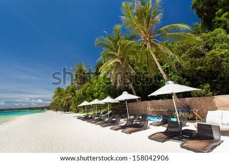Sun umbrellas and beach chairs on tropical coast, Philippines, Boracay  - stock photo