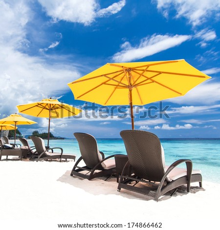 Sun umbrellas and chairs on beach - stock photo