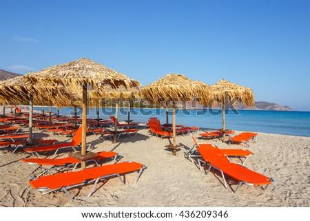 Sun umbrellas and chairs on beach - stock photo