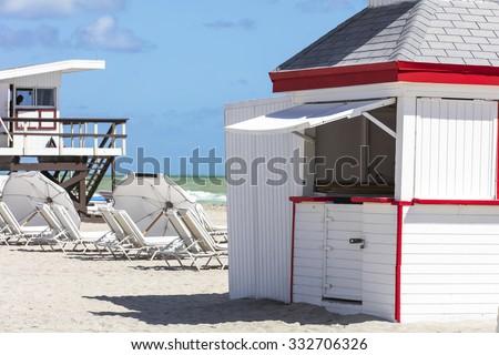 Sun umbrellas and rescue  buildings on the beach of ocean. Miami Beach, Florida. - stock photo