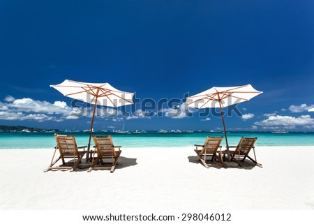 Sun umbrellas and wooden beds on tropical beach. Caribbean vacation - stock photo