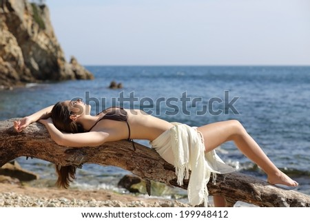 Sunbather beautiful woman sunbathing on the beach with the sea in the background