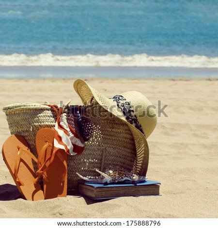 sunbathing accessories on sandy beach by the ocean, toned image - stock photo