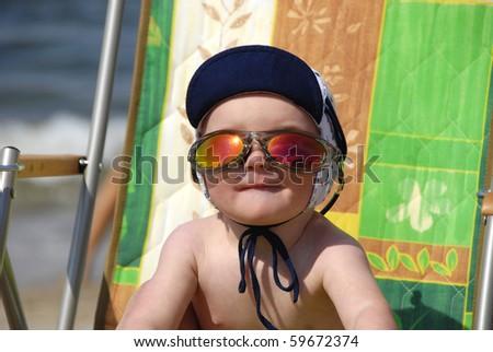 sunbathing baby in sunglasses on the deckchair - stock photo