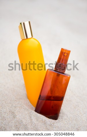 sunbathing concept - close up of suntan lotion bottles in sand - stock photo
