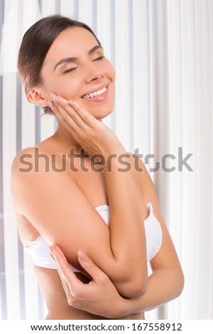 Sunbathing in solarium. Attractive young woman standing in tanning booth and touching face - stock photo