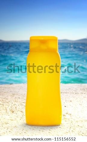 Sunbathing - suntan cream or oil on beach, background - stock photo
