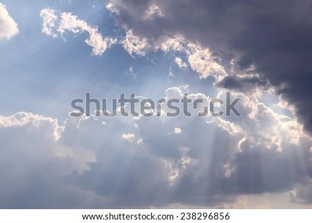 Sunbeam through the cloud on blue sky - stock photo