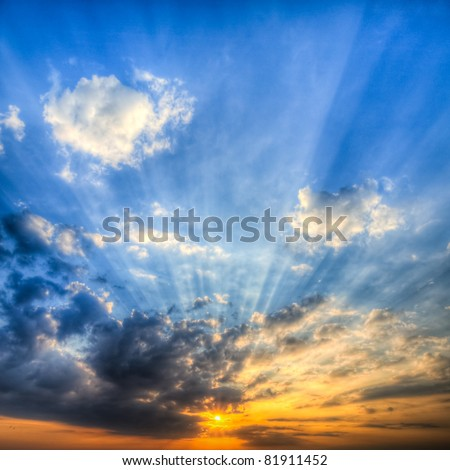 Sunbeams at sunrise created by low altitude clouds obscuring the sun - stock photo