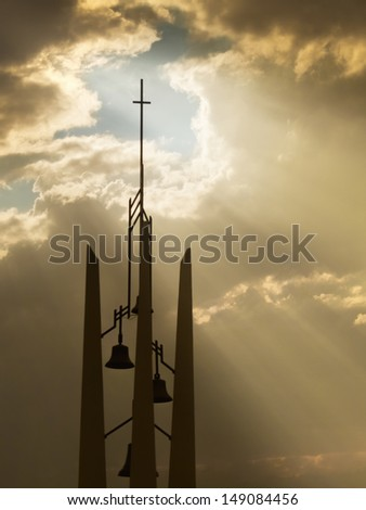 Sunbeams break through the storm clouds behind this Church Bell tower and Cross making an inspirational, christian scene - stock photo