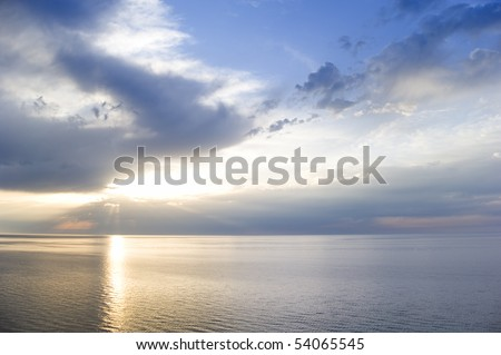 Sunbeams emanating from behind a clouds at sunset - stock photo