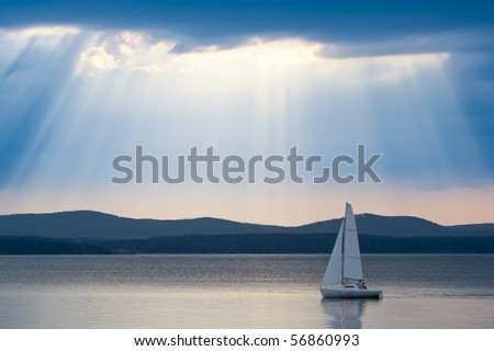 Sunbeams in the cloudy sky with one yacht in the foreground - stock photo