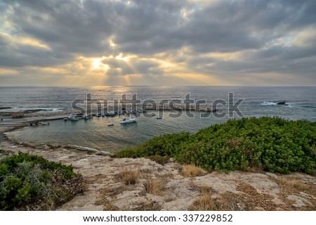 Sunbeams over sea and bay for fishing boats - stock photo