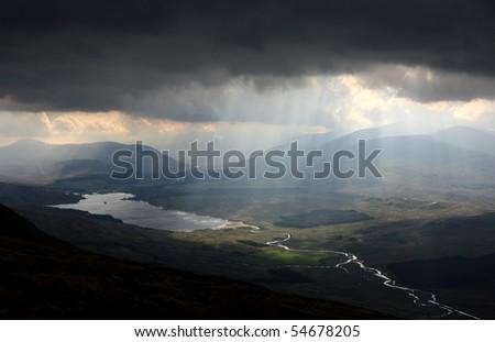 Sunbeams shining through dark clouds above Loch Tulla, Scotland - stock photo