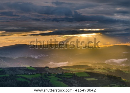 Sunbeams through the clouds at sunset in the mountains of San Roman, Cervantes, Lugo, Galicia - stock photo