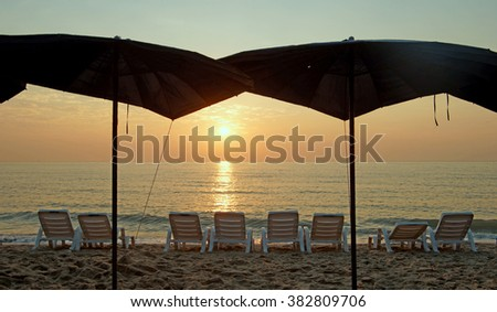 sunbed and beach umbrella on the beach with beautiful sunrise background