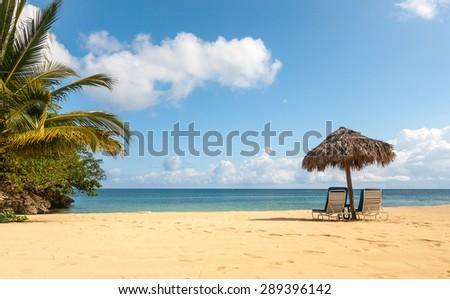 Sunbed and umbrella on a beautiful tropical beach - stock photo