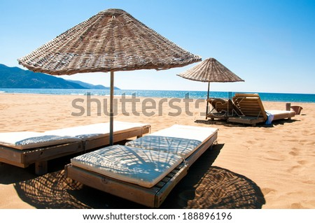 Sunbeds and rattan parasols on sandy seaside. - stock photo