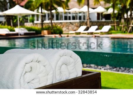 sunbeds and umbrellas near resort's pool - stock photo