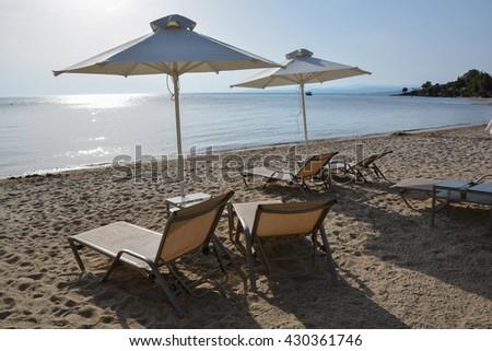 Sunbeds and umbrellas on a sandy beach, Halkidiki, Greece - stock photo