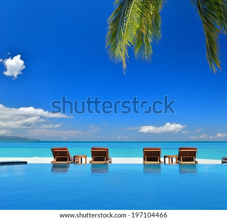 Sunbeds beside swimming pool in tropical beach resorts -- Summer vacation concept - stock photo
