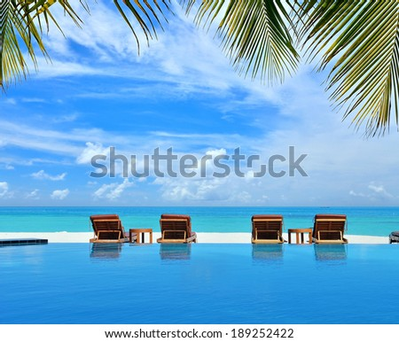 Sunbeds beside swimming pool in tropical beach resorts -- Tropical vacations concept - stock photo