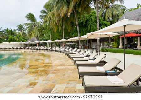 sunbeds beside the swimming pool in beach resort