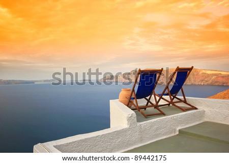 Sunbeds on Santorini's roofs at sunrise - stock photo