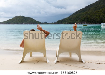 sunbeds on the beach in Seychelles and the couple's hands with rings on a background cloudy sky - stock photo