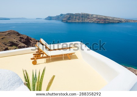Sunbeds on the beach. Santorini island, Greece. Beautiful summer landscape with sea view - stock photo