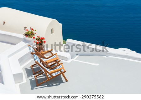 Sunbeds on the terrace of a hotel. Santorini island, Greece. Beautiful summer landscape with sea view - stock photo