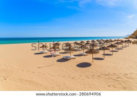 Sunbeds with umbrellas on sandy beach in Salema seaside town, Alrgarve region, Portugal - stock photo