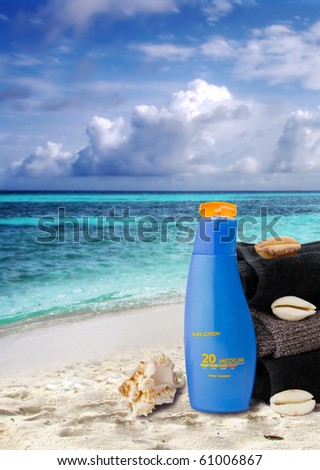 Sunblock lotion and black towels with ocean scene